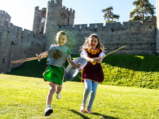 Boy and girl in medieval costume in front of Warwick Castle